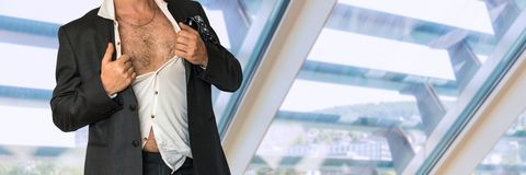Disheveled man in business suit with an unbuttoned shirt. In office Royalty Free Stock Images