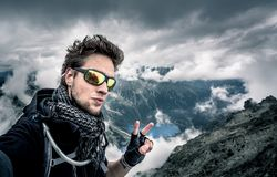 Disheveled man, with tousled hair on top of the mountain. Showing the peace sign, with lakes and low clouds in the background Royalty Free Stock Image
