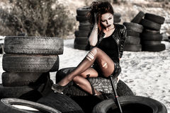 Disheveled redhead woman with a baseball bat. Disheveled redhead woman sitting with a baseball bat at the background of an old tires stock images