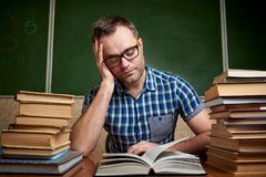 A disheveled tired unshaven young man with glasses holds his head and reads a book at the table with piles of books against the stock image