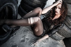 Disheveled woman between an old tires Stock Photography
