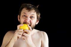 Dishevelled man eating a lemon Stock Photos