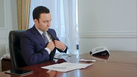 Dishonest businessman in suit looks back, counts money and takes some euro banknote stock image
