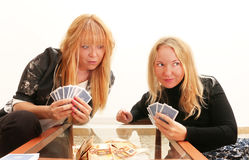 Dishonesty -  a cunning girl cheating her friend while playing card game for money Royalty Free Stock Image