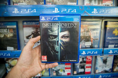Dishonored 2. Bratislava, Slovakia, circa april 2017: Man holding Dishonored 2 videogame on Sony Playstation 4 console in store Stock Images