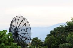 Dishs satellites noirs sur le fond de l'arbre et du ciel verts Photos libres de droits
