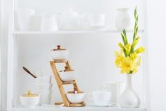 Dishvare blanco con las flores en estante de madera Imagen de archivo