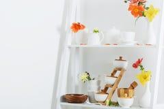 Dishware blanco con las flores en estante de madera Fotos de archivo libres de regalías