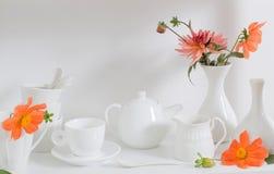 Dishware blanco con las flores en estante de madera Foto de archivo