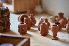 Dishware cerâmico no worktop e prateleiras na oficina da cerâmica, foco seletivo, close-up fotografia de stock