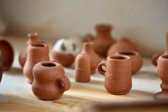 Dishware cerâmico no worktop e prateleiras na oficina da cerâmica, foco seletivo, close-up fotos de stock royalty free