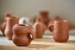 Dishware cerâmico no worktop e prateleiras na oficina da cerâmica, foco seletivo, close-up foto de stock