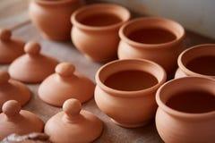 Dishware cerâmico no worktop e prateleiras na oficina da cerâmica, foco seletivo, close-up imagens de stock