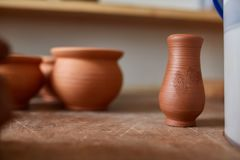 Dishware cerâmico no worktop e prateleiras na oficina da cerâmica, foco seletivo, close-up, profundidade de campo rasa imagem de stock