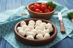 Dishware com bolas do mozzarella e tomates de cereja na tabela imagem de stock