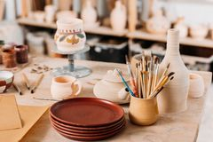 dishware e escovas cerâmicos na tabela de madeira foto de stock