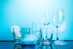 Dishware in the foam with reflection on blue background Royalty Free Stock Photos