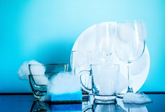 Dishware in the foam with reflection on blue background Stock Image