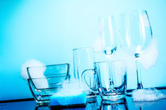Dishware in the foam with reflection on blue background Royalty Free Stock Photo