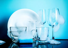 Dishware in the foam with reflection on blue background Royalty Free Stock Image