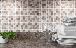Dishware- och gräsplanörtar på kökcountertop Royaltyfria Bilder