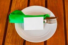 Dishware och tomt pappers- kort på tabellen i restaurang Arkivbilder