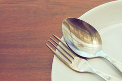 Dishware set on wood table with plate, spoon and fork Stock Photo
