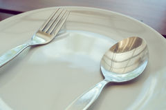 Dishware set on wood table with plate, spoon and fork Royalty Free Stock Images