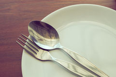 Dishware set on wood table with plate, spoon and fork Stock Photos