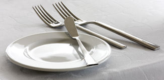 Dishware on a table. Knife, fork and plate on a table Stock Photo