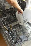 Dishwasher. Woman placing a dish in the dishwasher for cleaning Stock Photo