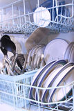 Dishwasher. A load of dishes ready for the cleaning Royalty Free Stock Photography