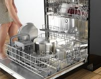 Dishwasher detail. Women shows inside and clean dishes and usage Royalty Free Stock Photography