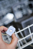 Dishwasher detergent. A hand holding a dishwasher detergent tablet, the dishwasher blurred in the background stock images