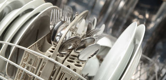 Dishwasher with Dishes. A dishwasher with clean dishes and utensils. Panoramic composition Royalty Free Stock Photography