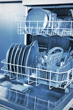 Dishwasher. Inside a dishwasher with plates and cutlery royalty free stock images