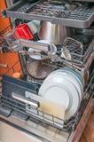 Dishwasher in kitchen and dirty dishes inside Stock Photos