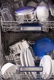 Dishwasher loades in a kitchen with clean dishes. And blue light royalty free stock image