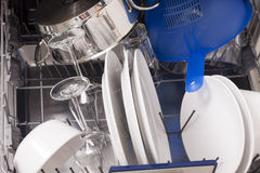 Dishwasher loades in a kitchen with clean dishes. And blue light royalty free stock photos