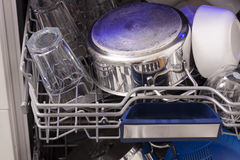Dishwasher loades in a kitchen with clean dishes. And blue light stock photo