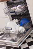 Dishwasher loades in a kitchen with clean dishes. And blue light royalty free stock images