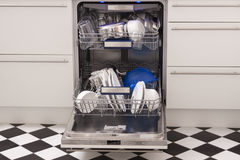 Dishwasher loads in a kitchen with clean dishes. And blue light stock images