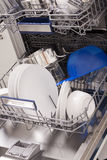 Dishwasher loads in a kitchen with clean dishes. And blue light royalty free stock photography