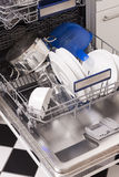 Dishwasher loads in a kitchen with clean dishes. And blue light stock image
