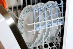 Dishwasher machine. Several washed plates in the open dishwasher machine Stock Photos