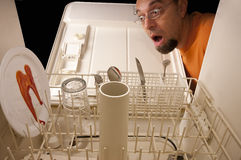 Dishwasher Prank. Middle age Caucasian man with a surprise look on his face when he sees a blood stained plate in the dishwasher. Prank concept, landscape Royalty Free Stock Image