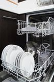 Dishwasher with white plates Stock Photos
