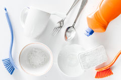 Dishwashing liquid, sponge, brush and tableware on white background top view. Dishwashing liquid and sponge on white background top view royalty free stock photography