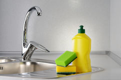 Dishwashing. Liquid with a sponge on kitchen sink Royalty Free Stock Photo