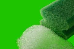 Dishwashing sponge. Green kitchen sponge with foam on green background stock images